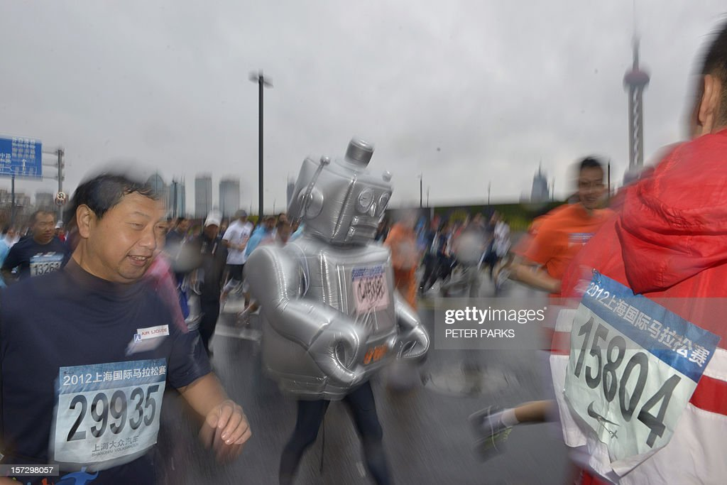 A runner dressed as a robot (C) participates in the Shanghai International Marathon on December 2, 2012. Thousands of runners started along Shanghai's famous Bund in the pouring rain for full, half and fun marathon events. AFP PHOTO/Peter PARKS