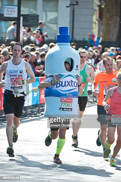 Runner dressed in a Buxton bottle costume passes by the Cutty Sark in Greenwich in the 2014 London Marathon on April 13 2014 in London England