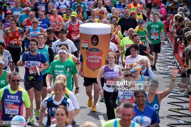 A runner dressed in a fancy dress pint of beer costume takes part in the 2016 London Marathon in central London on April 24 2016 / AFP / NIKLAS...