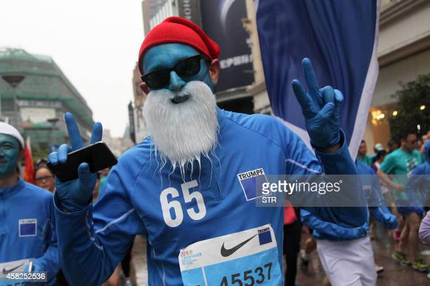 A runner dressed in a Smurf costume takes part in the 2014 Shanghai International Marathon in Shanghai on November 2 2014 Shanghai marathon kicked...