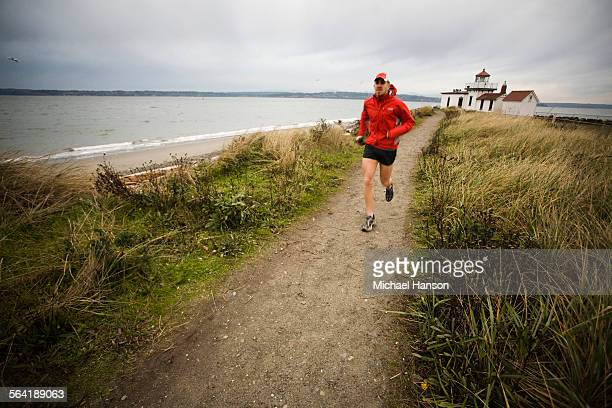 A runner follows a trail along the Puget Sound at Discovery Park, Seattle, WA.