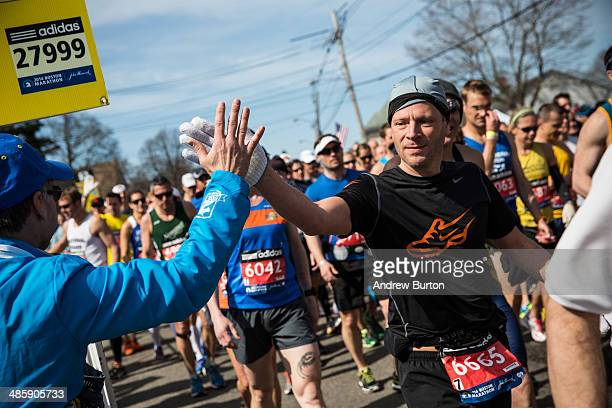 A runner gives a high five at the beginning of the Boston Marathon on April 21 2014 in Hopkington Massachusetts Today marks the 118th Boston Marathon...