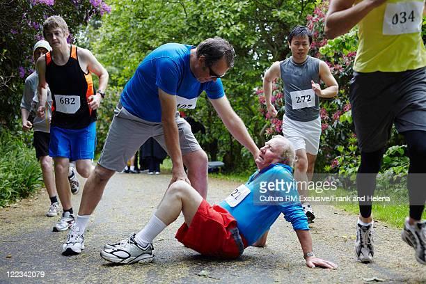 Runner helping older man in marathon