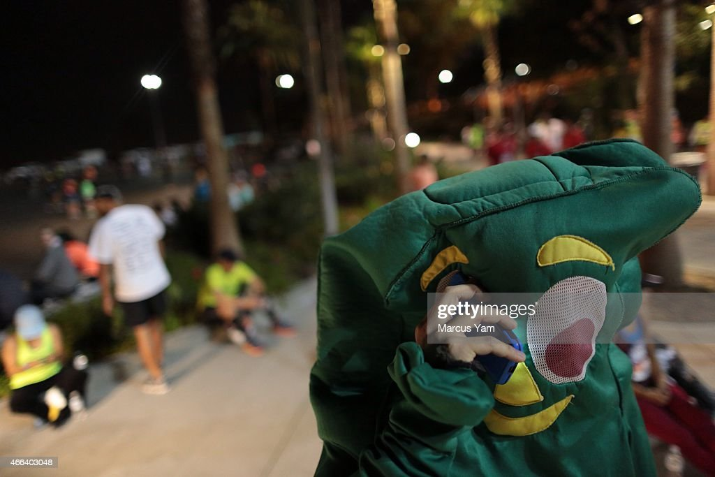 A runner in a Gumby costume talks on a cellphone at the start of the 30th LA Marathon at Dodger Stadium March 15 2015 in Los Angeles California