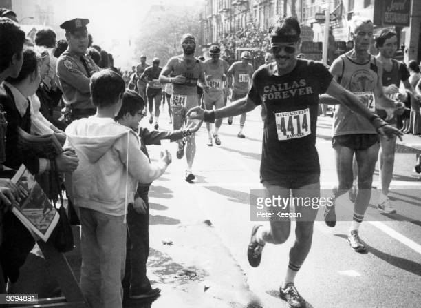 A runner in a New York marathon taking refreshment from a young onlooker His tshirt says 'Callas Forever'
