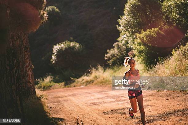 Runner in colorful sports wear jogging on a mountain trail