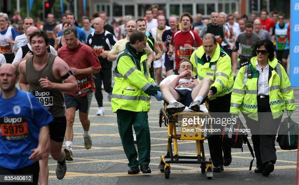 A runner is helped to the finishing line by medical staff in the Manchester 10k run during the BUPA Great Manchester Run and Great City Games in...
