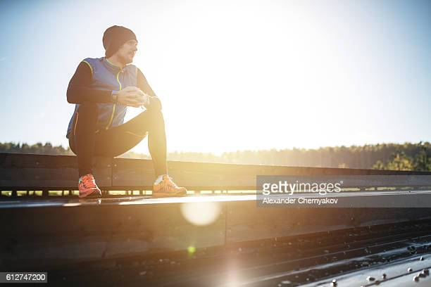 Runner is relaxing on a wooden stairs on sunrise