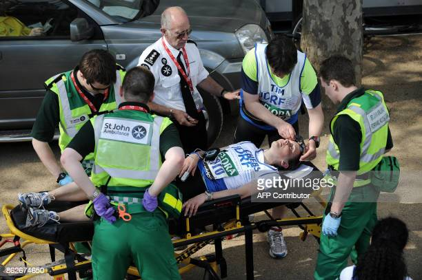 A runner is tended to by medics after crossing the finish Line near Buckingham Palace during the 2009 London Marathon April 26 2008 in London AFP...