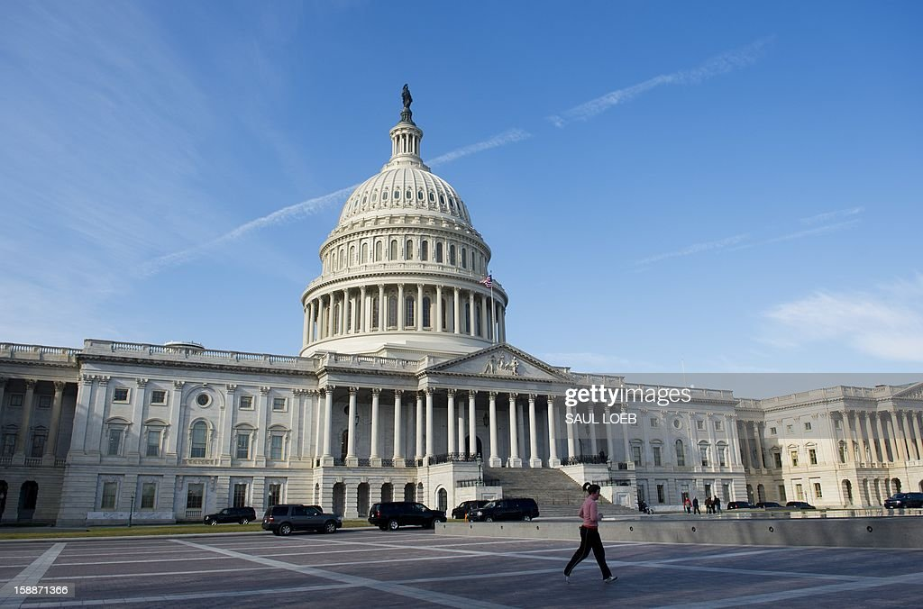 A runner jogs past the US Capitol in Washington, DC, on January 2, 2013, on the day after a compromise bill passed the US Congress, avoiding the 'fiscal cliff.' The agreement raises taxes on the rich and puts off automatic $109 billion federal budget cuts for two months. AFP PHOTO / Saul LOEB