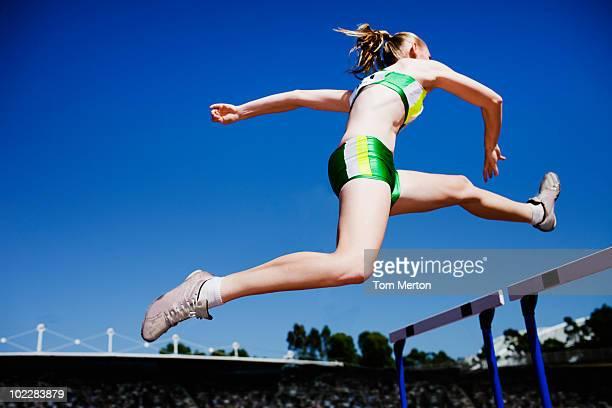 Runner jumping hurdles on track
