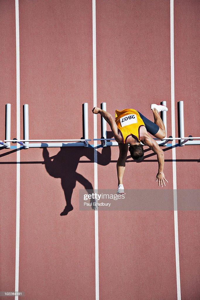 Runner jumping hurdles on track : Stock Photo