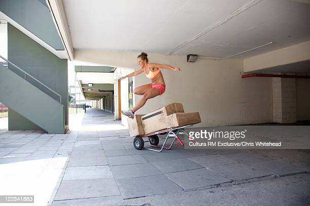 Runner jumping over boxes on city street