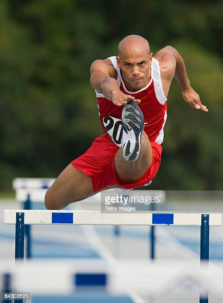 Runner jumping over hurdle