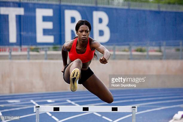 Runner jumping over hurdles on track
