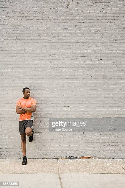 Runner leaning on wall