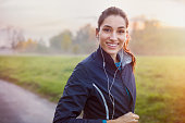 Young beautiful woman listening music at park while running. Portrait of smiling sporty girl with earphone looking at camera at park in autumn. Woman athlete looking at camera during winter sunset.'r