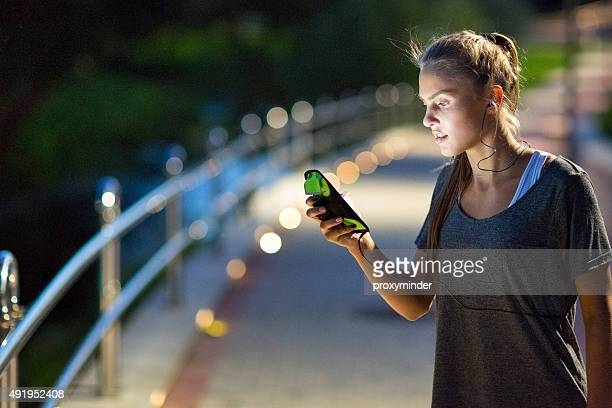 Runner listening to music and looking at phone