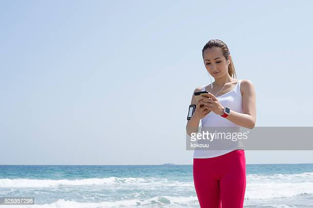 Runner looking at the smartphone at the seaside