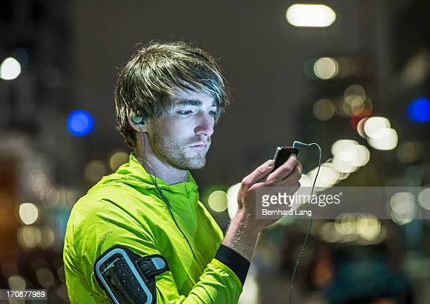 Runner looking on smartphone in city by night