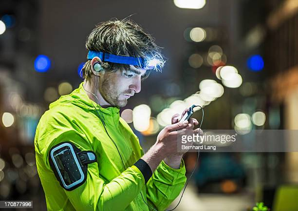 Runner looking on smartphone, wearing head torch