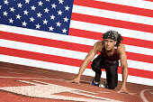 Runner on a track in starting block in front of US flag