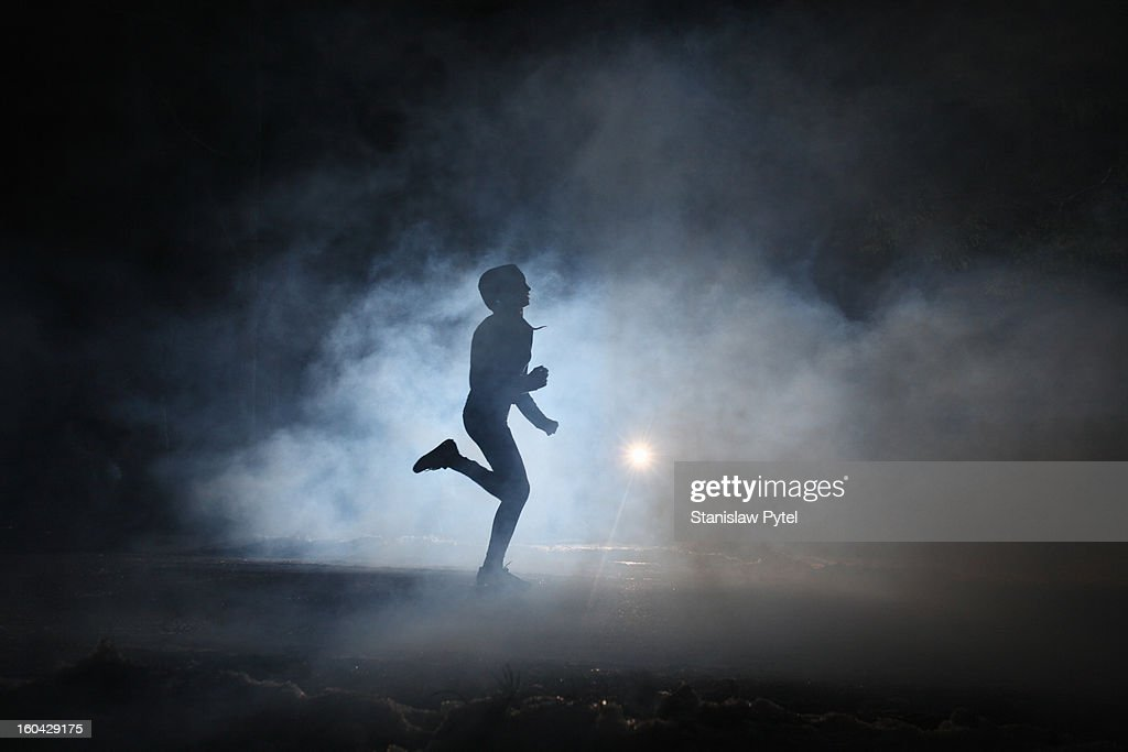 Runner on road in the fog at night : Stock Photo