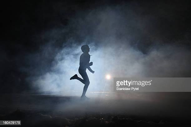 Runner on road in the fog at night