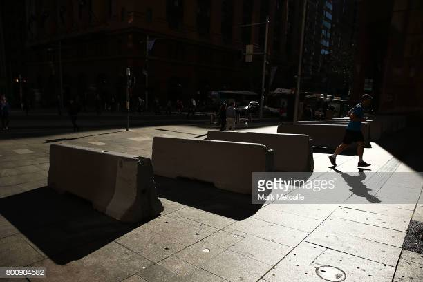 A runner passes newly installed anti terror bollards in Martin Place on June 26 2017 in Sydney Australia The large concrete blocks have been...