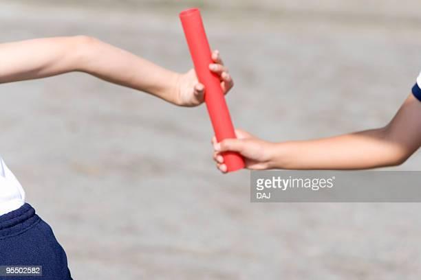 Runner passing baton