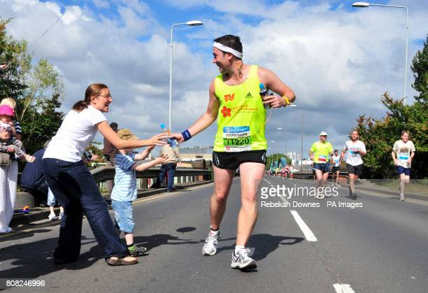A runner receives some Lucozade from his family