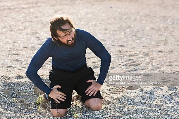 Runner resting on rocky beach
