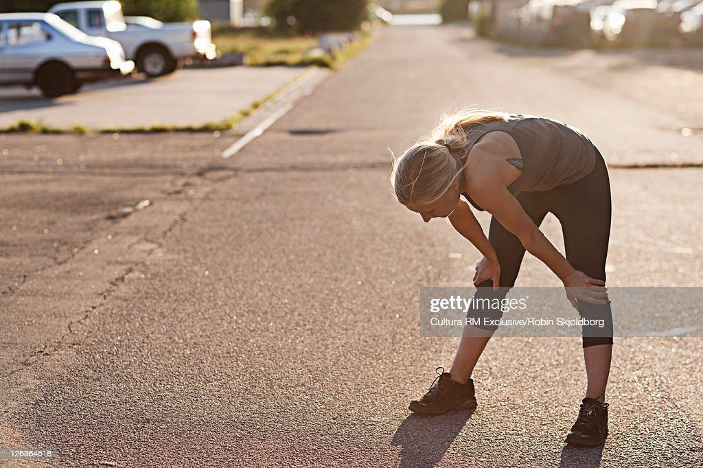 Runner resting on suburban street : Stock Photo