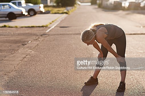 Runner resting on suburban street