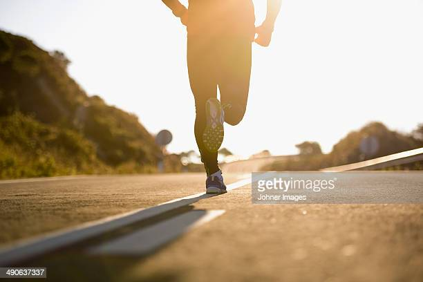 Runner running on road, low section