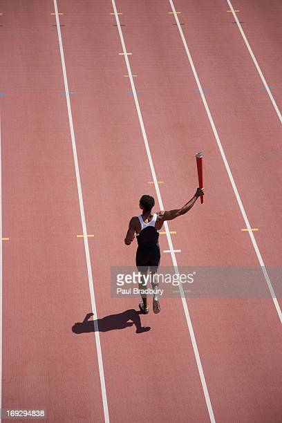 Runner running with torch on track