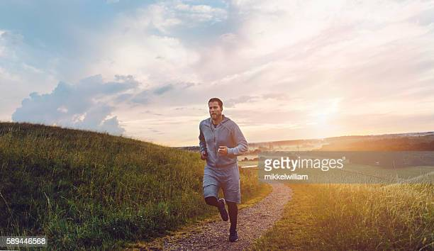 Runner runs outside on small road at sunset