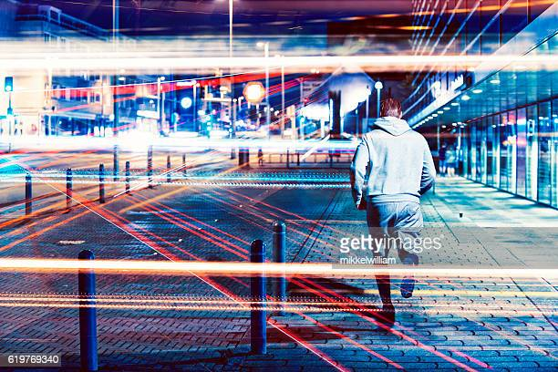 Runner runs through city at night with lots of lights