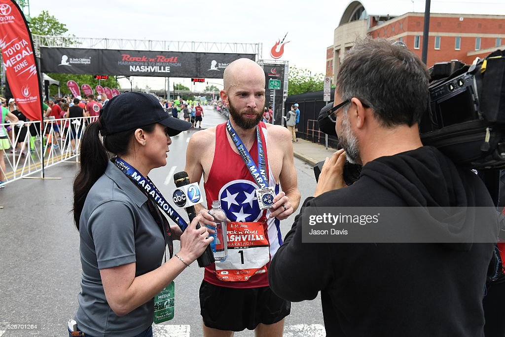 Runner Scott Wietecha is interviewed after he crosses the finish line at the St. Jude Rock 'n' Roll Nashville Marathon/Half Marathon and 5k where more than 34,000 participants weathered the rain during the 17th running on April 30, 2016 in Nashville, Tennessee.
