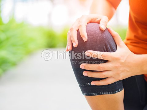 Runner sport knee injury. Woman in pain while running in the garden. : Stock Photo