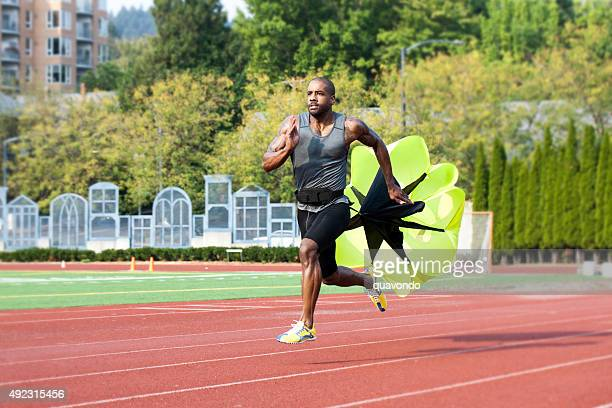 Runner Sprinting Down Track with Parachute