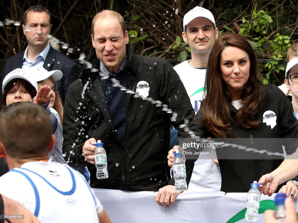 A runner squirts water towards Prince William, Duke of Cambridge and Catherine, Duchess of Cambridge as they hand out water to runners during the 2017 Virgin Money London Marathon on April 23, 2017 in London, England. The Duke and Duchess of Cambridge and Prince Harry, are spearheading Heads Together, in partnership with eight leading mental health charities, that are tackling stigma, raising awareness, and providing vital help for people with mental health problems.