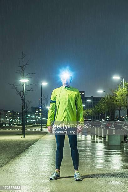 Runner standing in urban area, raining