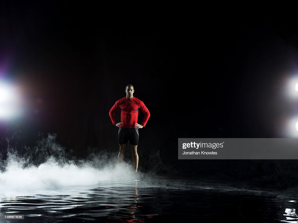 Runner standing in water, misty night : Stock Photo