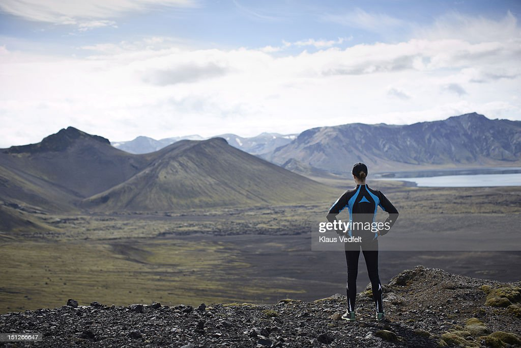 Runner standing on mountain looking out : Stock Photo