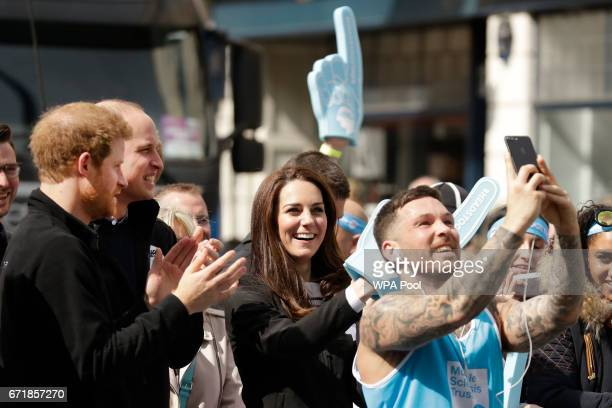 A runner stops to take a selfie backdropped by Britain's Prince Harry Prince William Duke of Cambridge and Catherine Duchess of Cambridge cheering on...