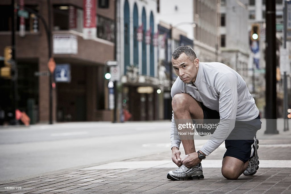 A runner stops to tie his shoe : Stock Photo