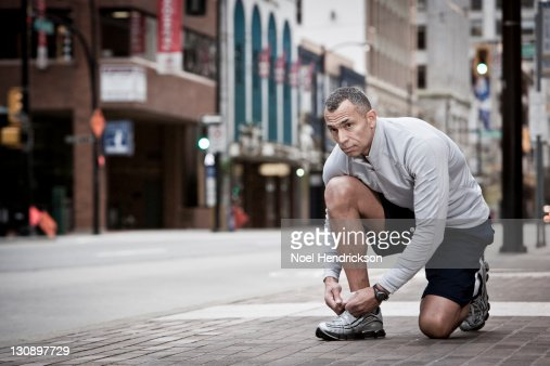 A runner stops to tie his shoe