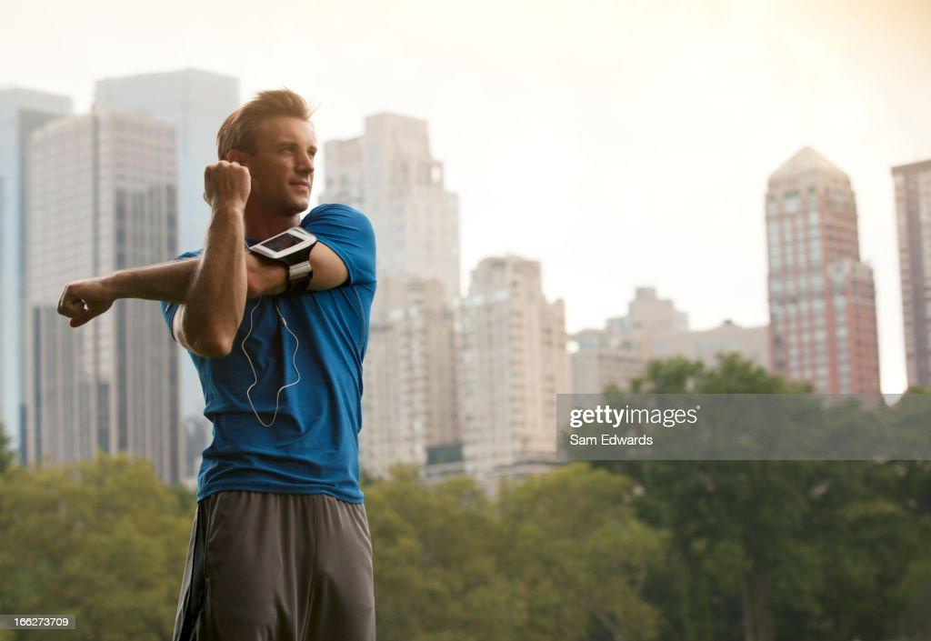 Runner stretching in urban park : Stock Photo