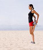 Runner stretching on beach